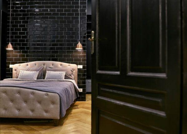 Fotografii de design interior ce prezinta o camera decorata cu negru iar printr-o usa intredeschisa se vede un pat