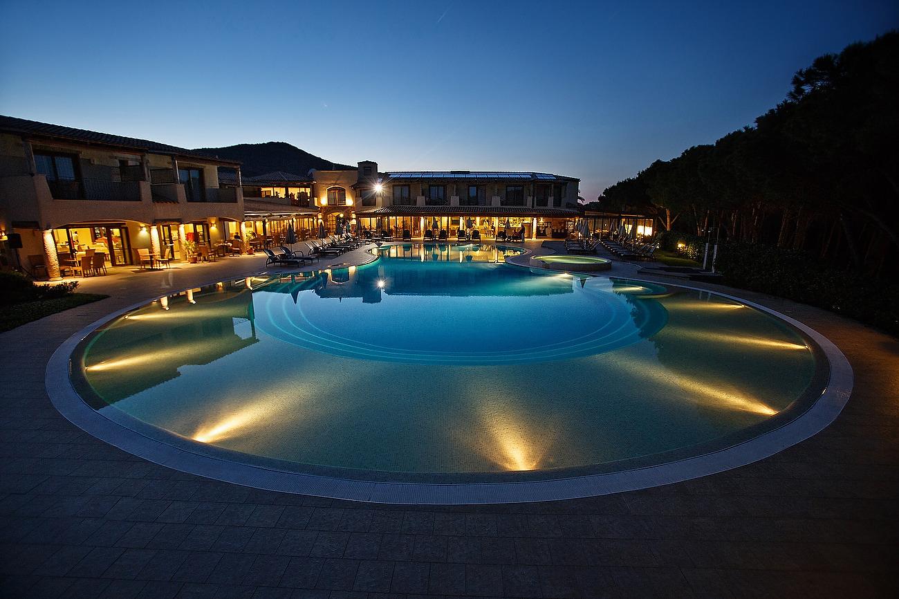 Imagine de ansamblu cu piscina si hotel noaptea
